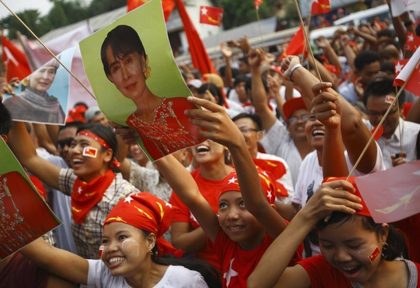 Supporters of the NLD party cheer as they watch increasing votes on a screen at the roof of the NLD office in Yangon