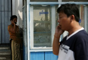 A man talks on his mobile phone next to a woman talking at a public phone shop in central Yangon