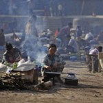 Refugees from Myanmar's Bhamo city cook their meals at a rescue camp in the Chinese southwestern border city of Ruili
