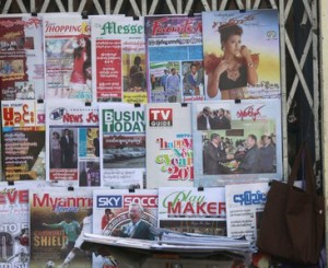 A woman reads a book as she sells newspapers and journals by the street side in Yangon