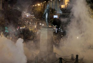 Tear gas fired by riot police at protesters fill the air during clashes at Talaat Harab square in downtown Cairo