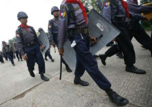 Policemen keep guard outside a stadium where soccer teams were playing in Yangon May 16, 2009.