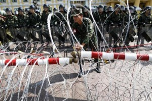 A security personnel adjusts razor wire as anti-government protesters arrive to the Defense Ministry in central Bangkok