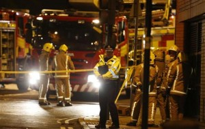Rescue workers gather near the scene where a police helicopter crahed onto the roof of a pub in Glasgow