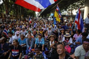 Anti-government protesters sit on the road outside the national police headquarters where they protest in Bangkok