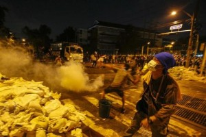 Anti-government protester throws tear gas canister towards police during clashes near Government House in Bangkok