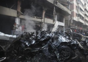 People attempt to extinguish a fire at the site of an explosion in Beirut's southern suburbs