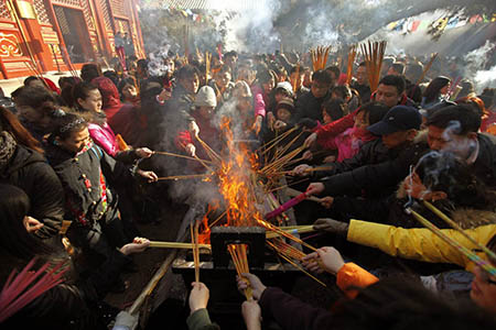 Locals burn incense to pray for good fortune on the first day of the Chinese Lunar New Year at Yonghegong Lama Temple in Beijing