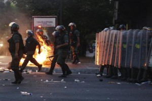 Riot police walk past a barricade of burning garbage during a protest against Venezuela's President Nicolas Maduro's government in Caracas