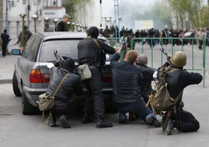 Pro-Russian armed men take cover behind a car near the local police headquarters in Luhansk