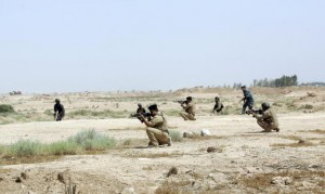 Members of Iraqi security forces take positions during patrol looking for militants of ISIL west of Kerbala