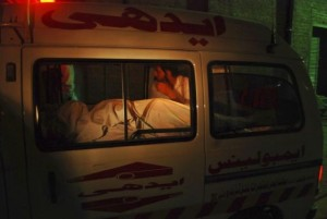 A man sits beside the body of a woman who was killed on board a PIA plane, as the ambulance carrying them arrives at a hospital in Peshawa