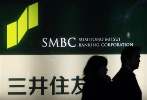 People walk past a signboard of Sumitomo Mitsui Banking Corporation in Tokyo