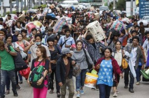 Cambodian migrant workers carry belongings as they walk to cross border at Aranyaprathet in Sa Kaew