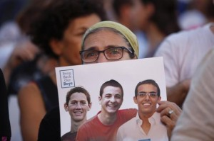 An Israeli woman holds a sign with images of three missing Israeli teenagers, at a rally in Rabin Square in the coastal city of Tel Aviv