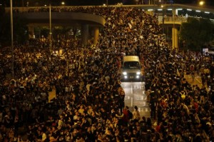 A vehicle drives among protesters blocking the main street to the financial Central district, outside the government headquarters, in Hong Kong