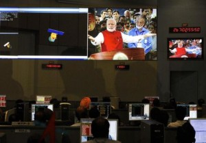 ISRO scientists and engineers watch PM Modi on screens after India's Mars orbiter successfully entered at their Spacecraft Control Center in Bangalore
