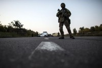 A Ukrainian soldier stands guard on a road during a prisoners-of-war (POWs) exchange, north of Donetsk, eastern Ukraine
