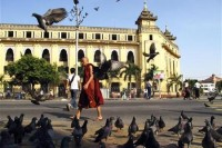 A Buddhist monk walks past the City Hall in downtown Yangon