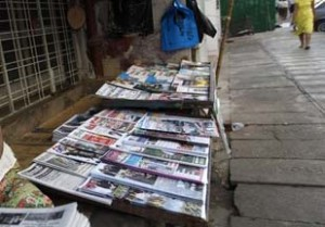 A woman arranges newspapers to sell by the street side in Yangon