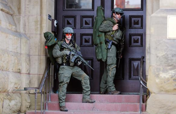 Armed RCMP officers guard the front of Langevin Block on Parliament Hilll following a shooting incident in Ottawa