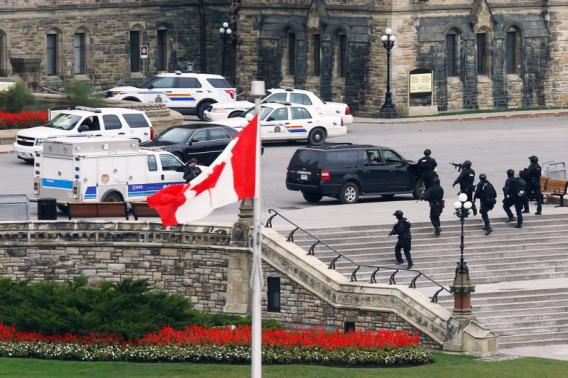 Armed RCMP officers head in to Centre Block on Parliament Hilll following a shooting incident in Ottawa