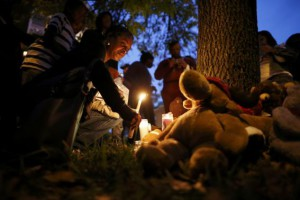 A woman places candles at the base of a tree at a vigil at the Shaw Market in St. Louis