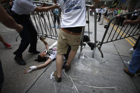 Anti-Occupy Central protesters drag a metal fence over a pro-democracy protester at the main protest site in Admiralty in Hong Kong
