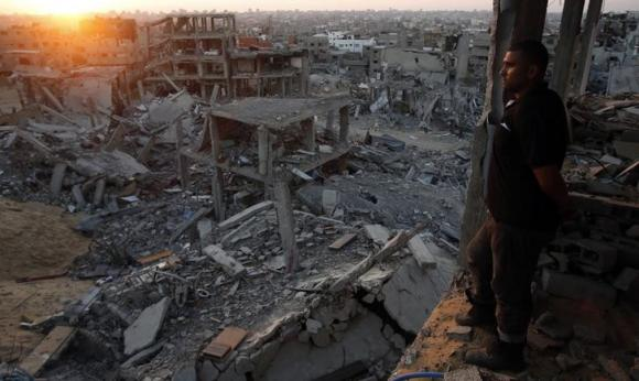 A Palestinian man looks out of his heavily damaged house at neighbouring houses which witnesses said were destroyed during the Israeli offensive, in the east of Gaza
