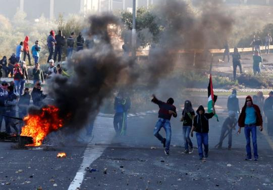 Israeli Arab youths throw stones during clashes with Israeli police at the entrance to the town of Kfar Kanna