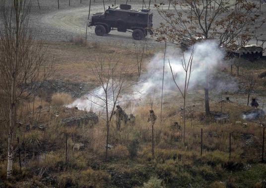 Indian army soldiers search for suspected militants as smoke rises from a bunker after a gunbattle at Mohra, in Uri