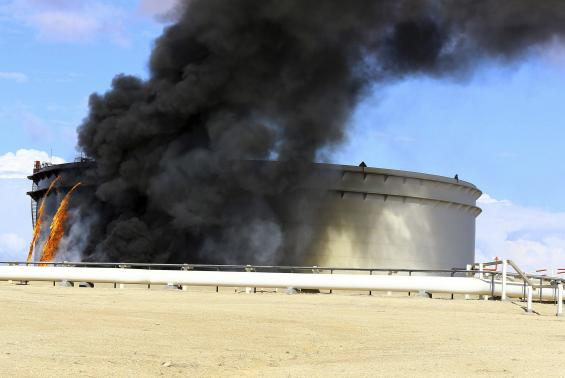 Black smoke billows out of a storage oil tank in the port of Es Sider in Ras Lanuf