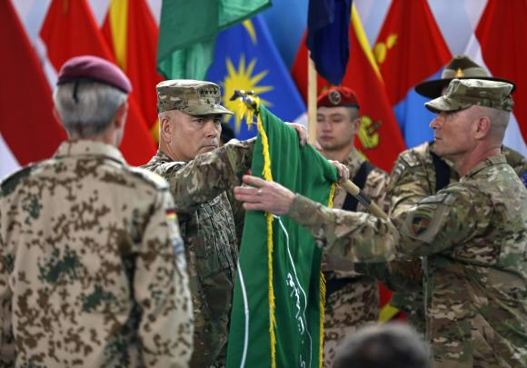 U.S. General John Campbell, commander of NATO-led International Security Assistance Force (ISAF), folds the flag of the ISAF during the change of mission ceremony in Kabul