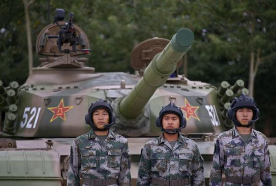Soldiers of People's Liberation Army stand in front of a tank in a drill during a organized media tour at a PLA engineering school in Beijing