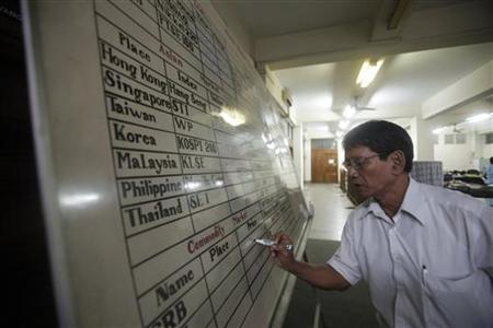 An office staff writes on a white board at the Myanmar Securities Exchange Centre in Yangon