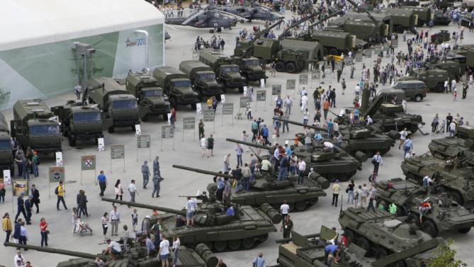 Visitors walk near exhibits, which are on display at the Army-2015 international military-technical forum in Kubinka