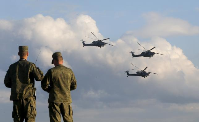 Russian servicemen watch Mi-28 military helicopters of the Berkuti aerobatic team fly during the opening of the Army-2015 international military forum in Kubinka