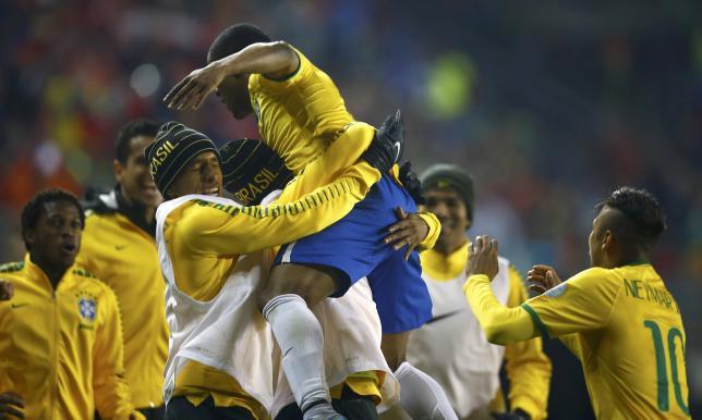 Brazil's Douglas celebrates with teammates after scoring against Peru during their first round Copa America 2015 soccer match at Estadio Municipal Bicentenario German Becker in Temuco