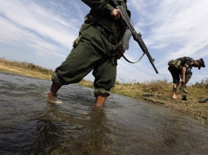 A soldier from the Kachin Independence Army puts on his shoes as he and his comrade cross a stream towards the front line in Laiza