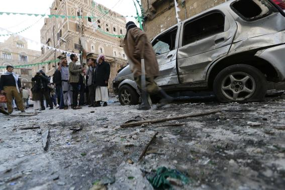 People gather at the site of a bomb explosion in Sanaa